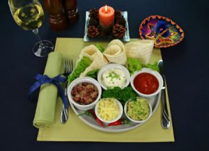 Mexican vegetarian platter with tortillas, guacamole, refried beans, cheese, sour cream and tomato salsa,